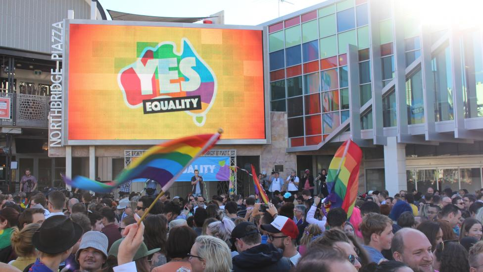 People celebrate the Yes vote, waving LGBQTI flags and a large screen in the background has YES displayed