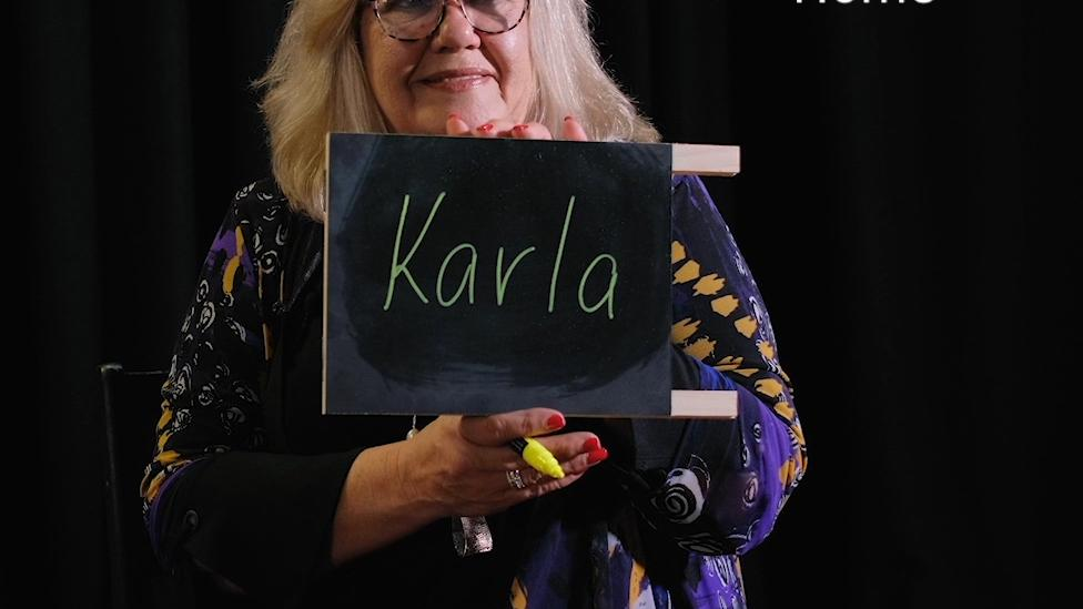 """""""A woman holds up a small chalkboard that reads 'Karla'. Text reads 'Home'."""""""