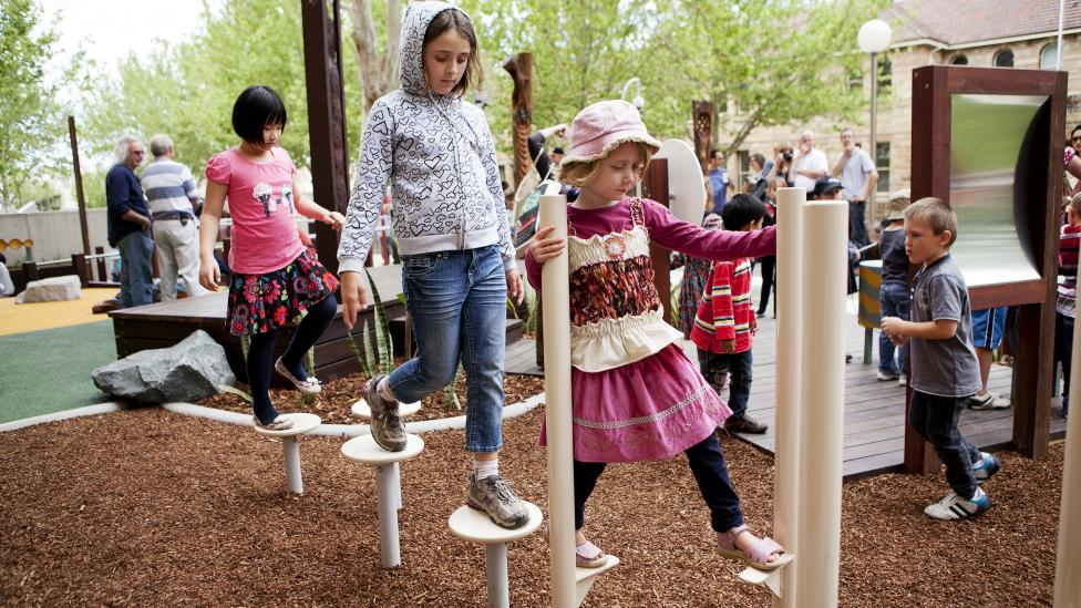 Children walking on stilt-like equipment in a play space