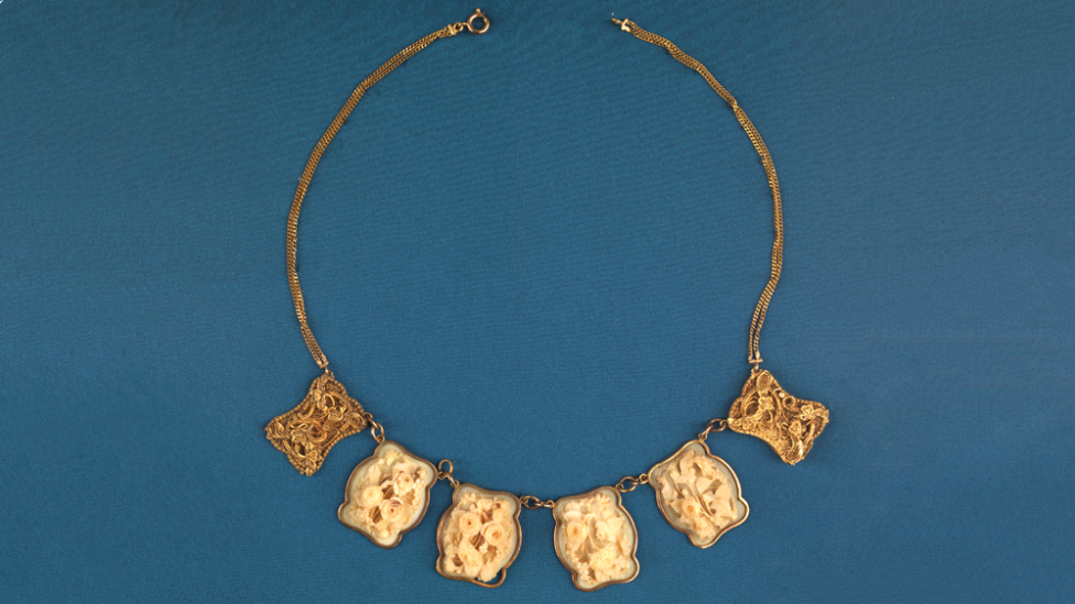 """""""A gold and ivory necklace."""""""
