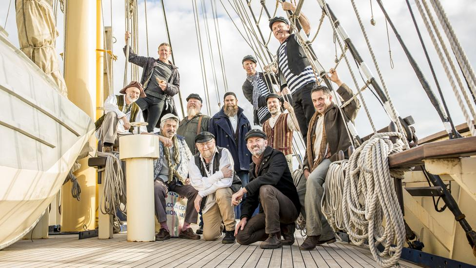 11 men grouped on a ship's deck, dressed in seafaring ware.