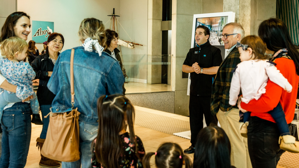 A group of visitors listening to a Museum staff member.