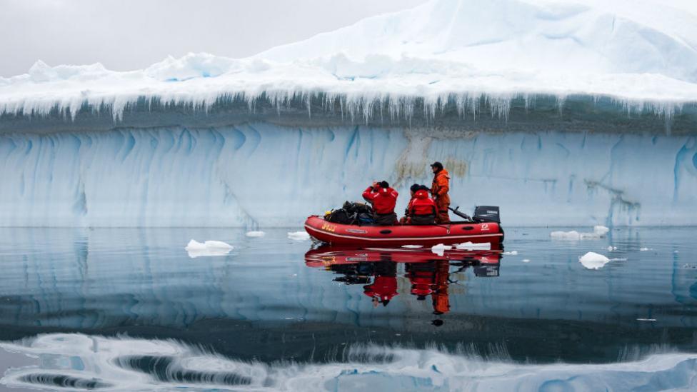 """Five explorers in Antarctica in a boat."""