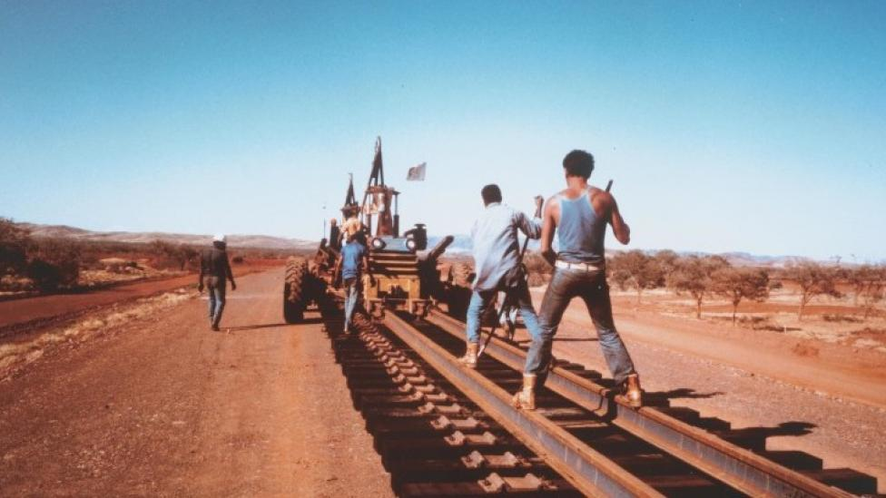 """""""A group of men are laying a railroad track in the outback."""""""