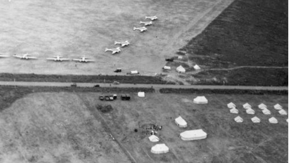 A black-and-white aerial photograph of aeroplanes in a field