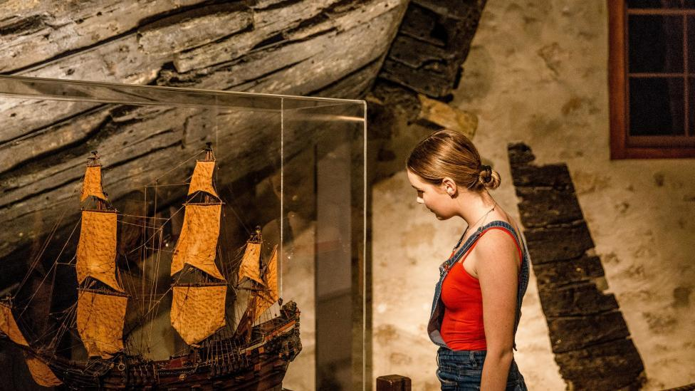 A young woman examines a museum showcase containing a model ship