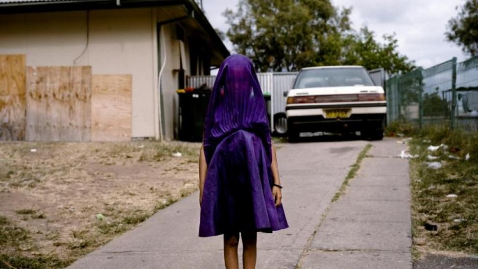 Laurinda, a young Kamilaroi girl from Moree, New South Wales, plays with her purple dress while she waits for the bus that will take her to Sunday School. She is among the many socially isolated young women in disadvantaged communities in Australia facing