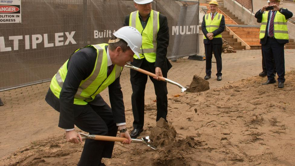 Premier McGowan bending with a ceremonial shovel and Minister Templeman standing to his left.  They are turning sod by digging the soil at the site of the New Museum.  Both are wearing fluro yellow vests and hard hats.
