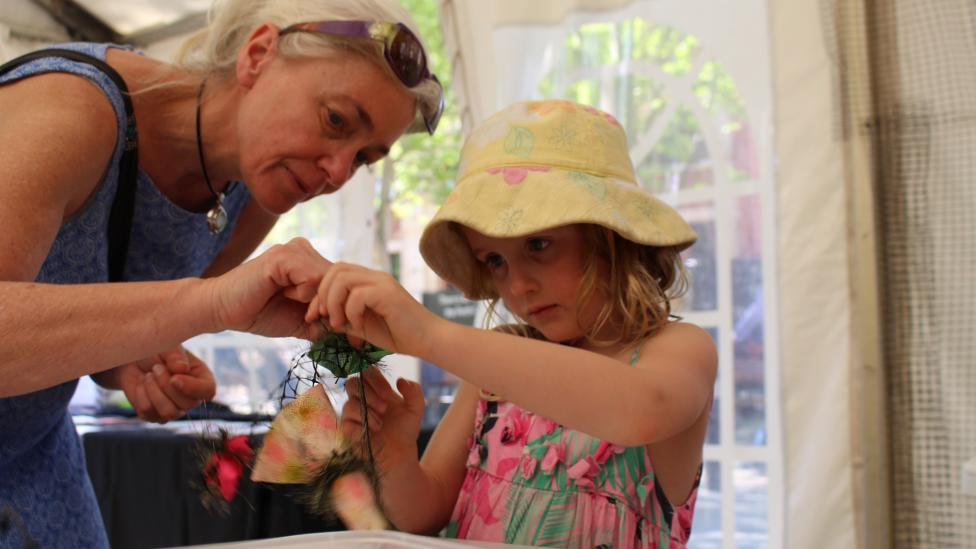 A woman and a young girl work on their contribution to the coral reef at AWESOME Festival