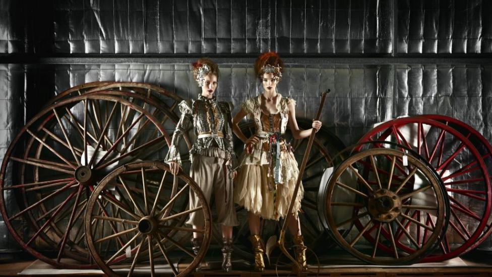 Two female models posing in front of large wheels