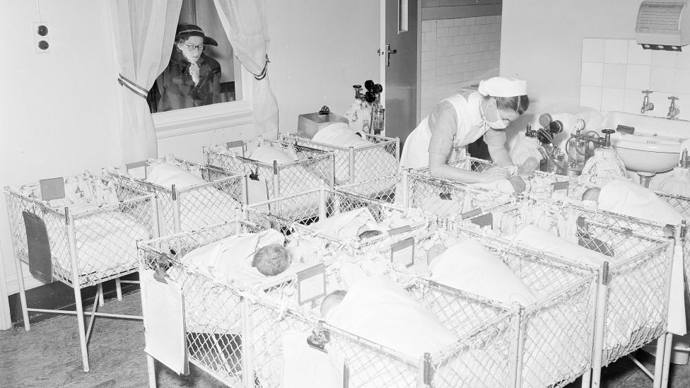 A crèche in a large metropolitan hospital with babies laying in small cots, 1954.