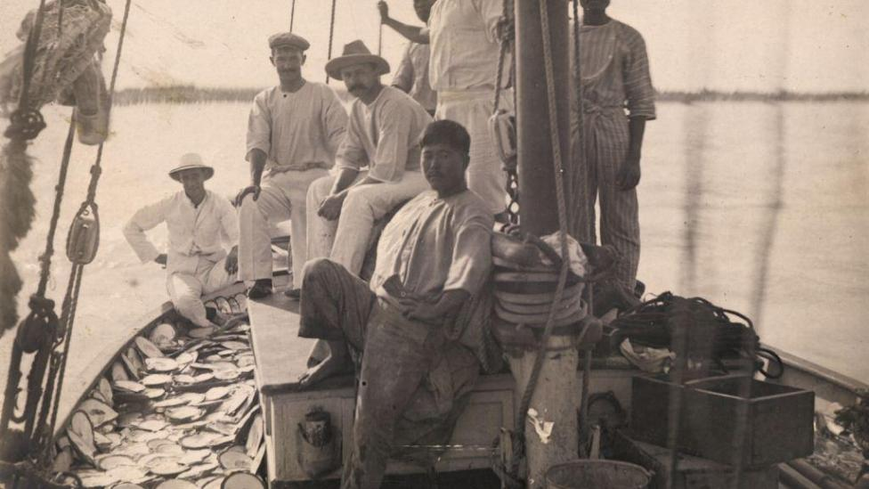Seven men on a pearl lugger with pearlshells on the deck