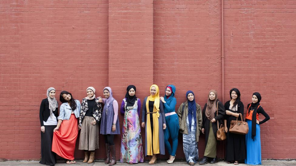 A group of Muslim women standing in front of a brick wall