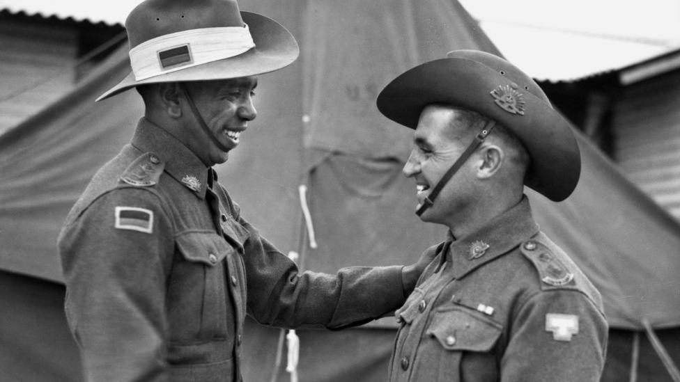 Lieutenant Reg Saunders (left) and Lieutenant Tom Derrick VC DCM, congratulate each other face-to-face following their graduation from the Office Cadet Training Unit at Seymour, 25 November 1944.