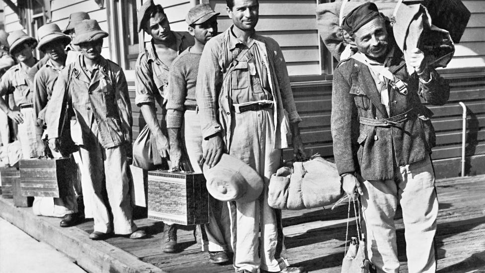 Italian prisoners of war carrying their their luggage wait to board a train bound for an Australian camp in 1943