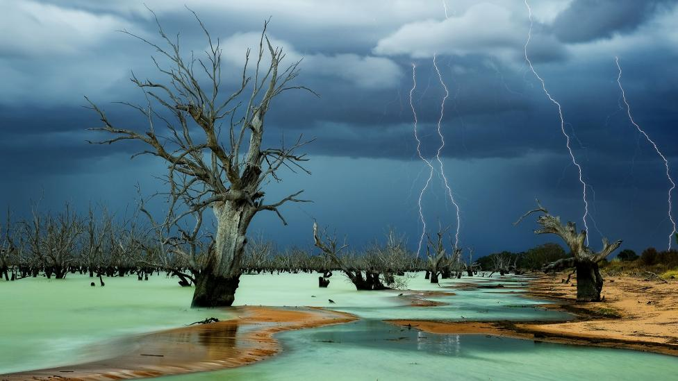 A dramatic storm taking place over a stark Australian outback lanscape
