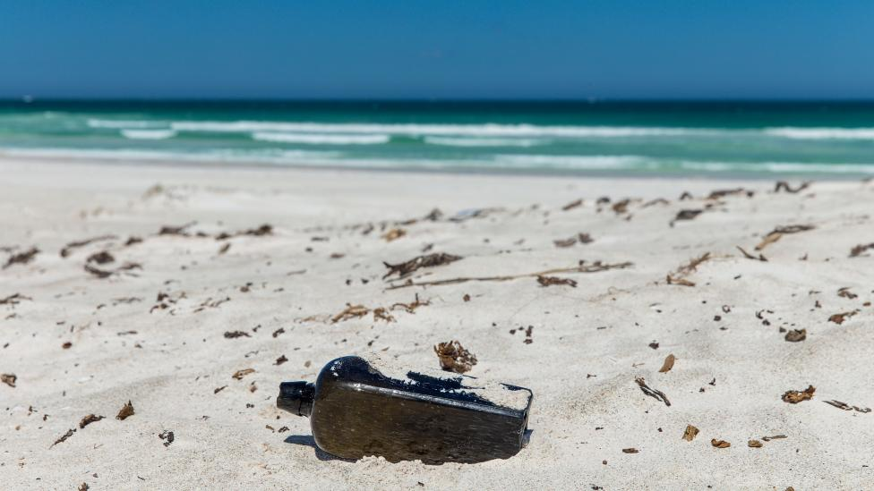 """The bottle is half submerged in sand in the foreground, with crashing waves in the background."""