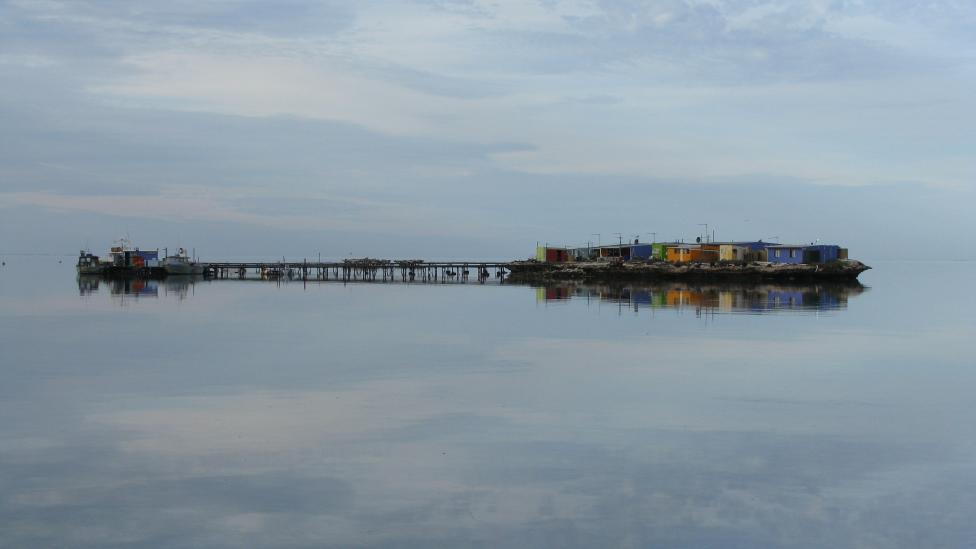 The Abrolhos Islands at a sunrise showing a reflection of the islands against the calm water