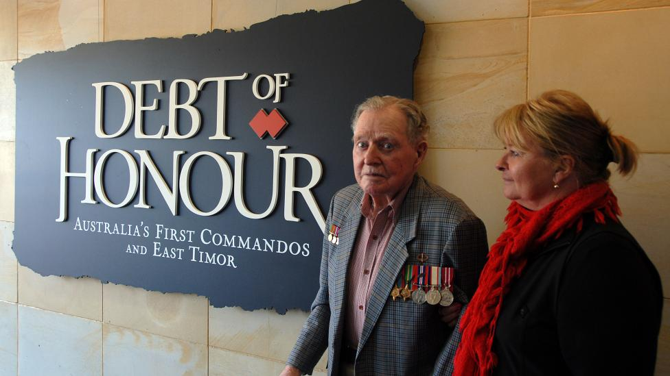 Two people standing near the entrance to exhibition 'Debt of Honour'