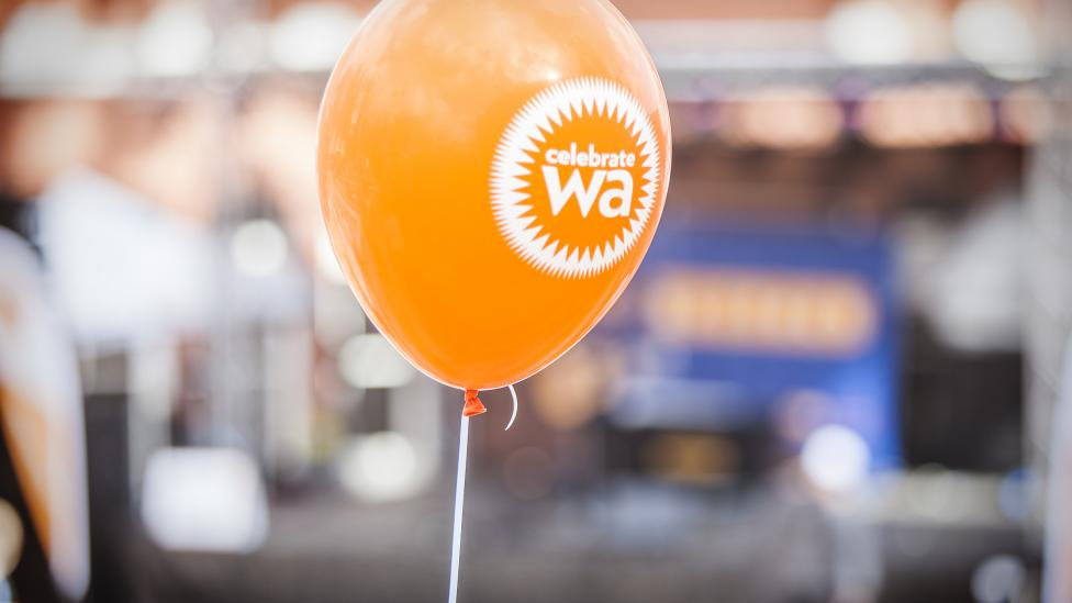 An orange balloon with Celebrate WA written on it
