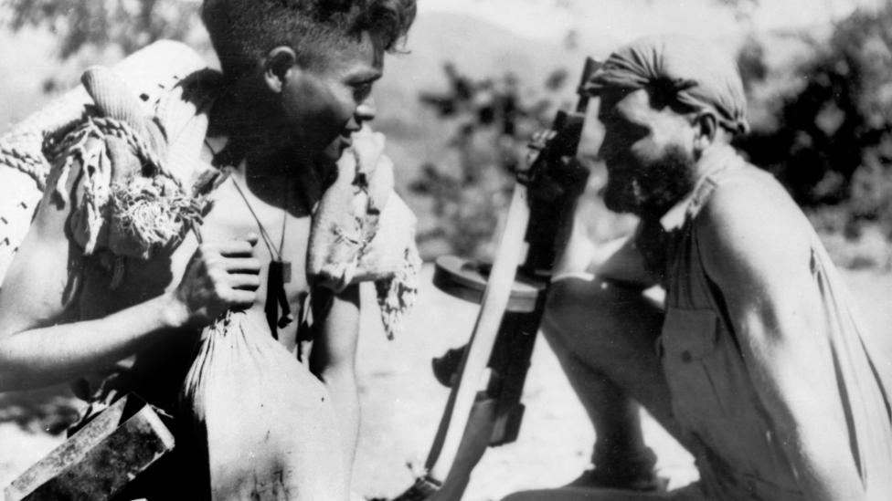Australian soldier sitting next a criado during World War Two in East Timor