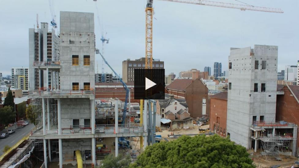 'View of a construction site with two tall thin concrete towers and a yellow crane in between them.'