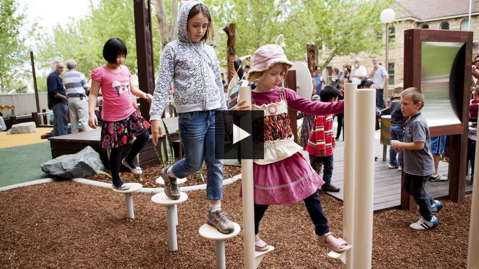 Children walking on stilt-like play equipment