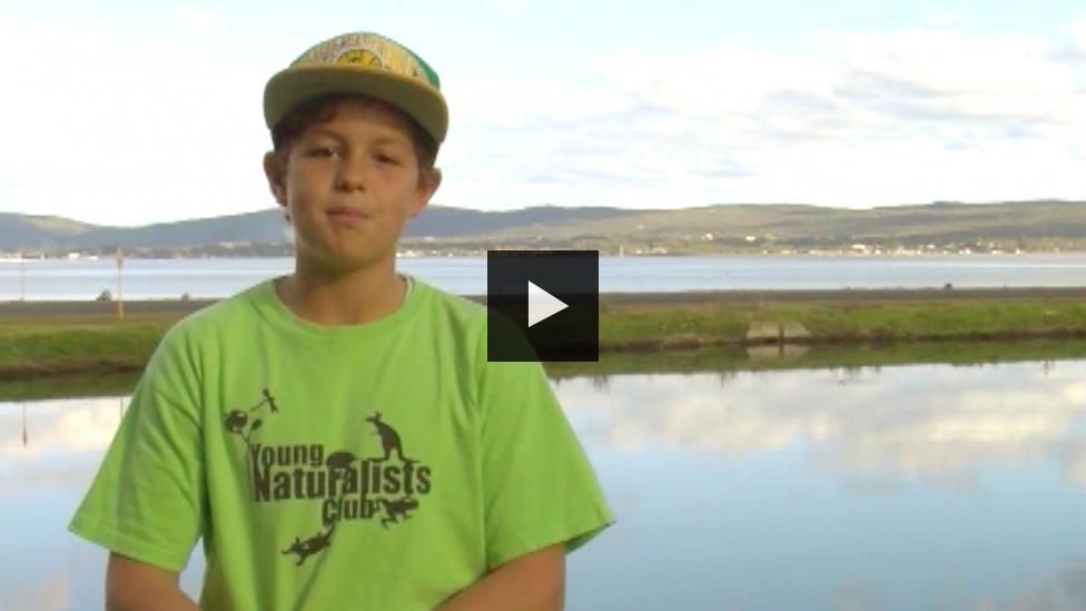 Boy in Young Naturalists Club T-Shirt stand in front of a lake and hills